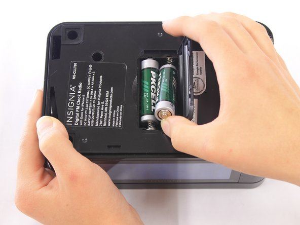 Remove the two AA batteries by pressing the end opposite of the spring towards that spring and lifting up.