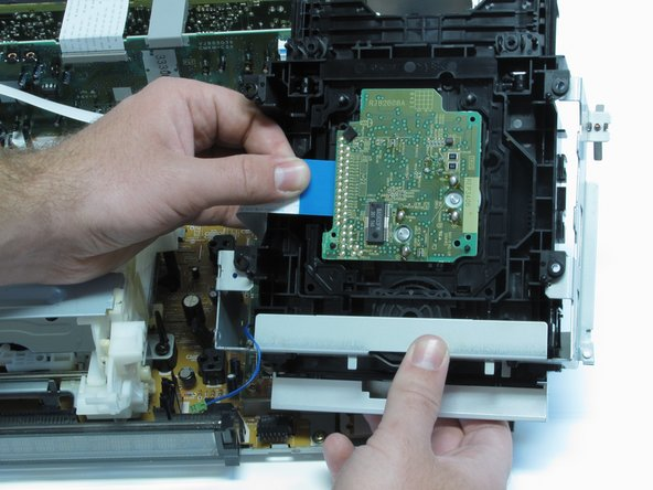 Slowly turn over the DVD drive and remove the electronic strip in the bottom as shown in image three.
