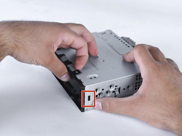 Apply small amount of pressure inward with a plastic opening tool to release bottom clip.