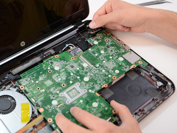 Image 3/3: To completely remove the motherboard from the laptop casing locate underneath the top right-hand corner an external cable and use your hand to unplug it as indicated in the picture.