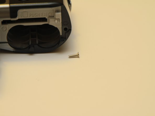 Remove the one coarse thread screw underneath the battery cover.