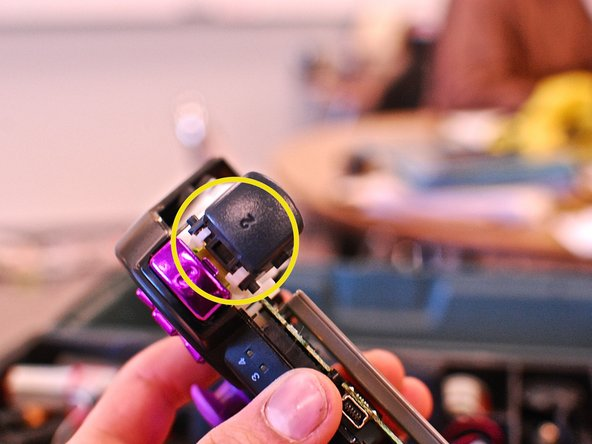 Your trigger buttons slide out, and the new ones slide in. The bottom L2 and R2 buttons have a little bar that clicks in, and out of he holder as well (circled in yellow).