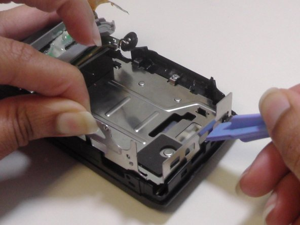 Use the plastic opening tool to assist you in separating the metal frame from the back cover of the camera.
