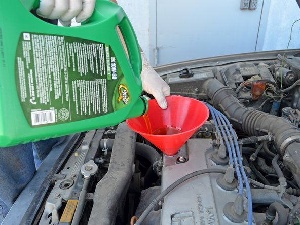 Pour 4 quarts of 10W-30 oil* into the engine. Use one hand to stabilize the funnel to help prevent spills.