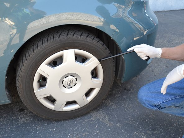 Loosen the lug nuts on the passenger side front wheel a half turn with a 22 mm wrench or tire iron.