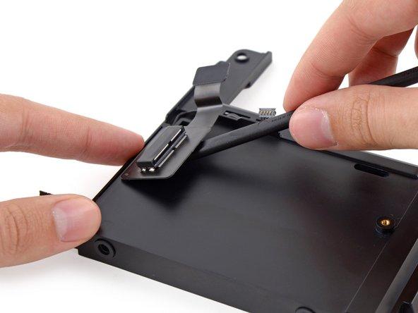 Schiebe das flache Ende des Spudgers unter  das Kabel zur SSD, um es aus der Klebeverbindung am Laufwerkseinschub zu lösen.