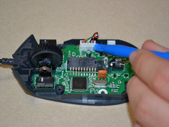 Use the plastic opening tool to pry the white cable jack away from the motherboard.