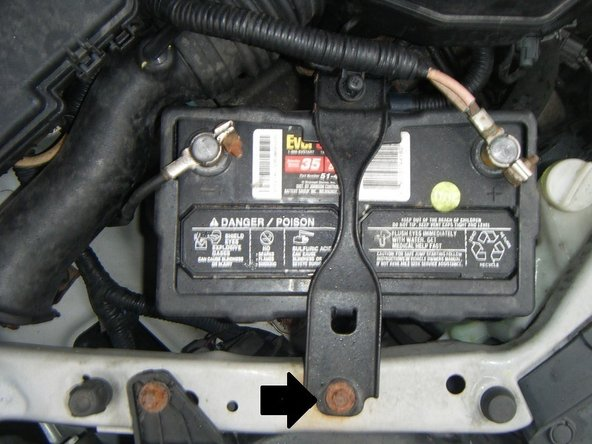 Using a socket wrench, remove the battery bracket from the top of the battery.