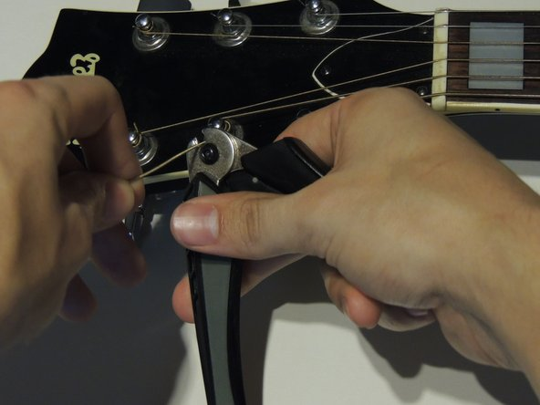 Using guitar string cutters, leave between a quarter inch to half of an inch of string so the excess string does not get in the way.