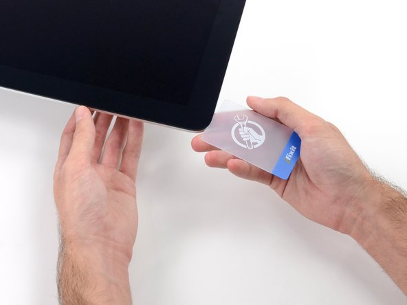 Insert a second plastic card into the gap between the display and frame near the top left corner of the iMac.