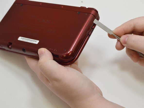 Using the Phillips #000 screwdriver, loosen the screws on the back cover.