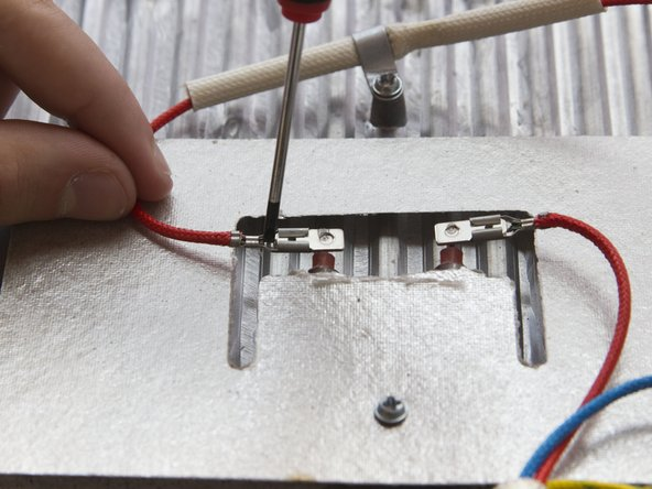 Simultanously press down the clip and pull the red wire to disconnect the red wire from the heating element.