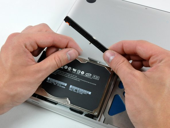 Lift the hard drive by its pull tab enough to grab and remove the retaining bracket.