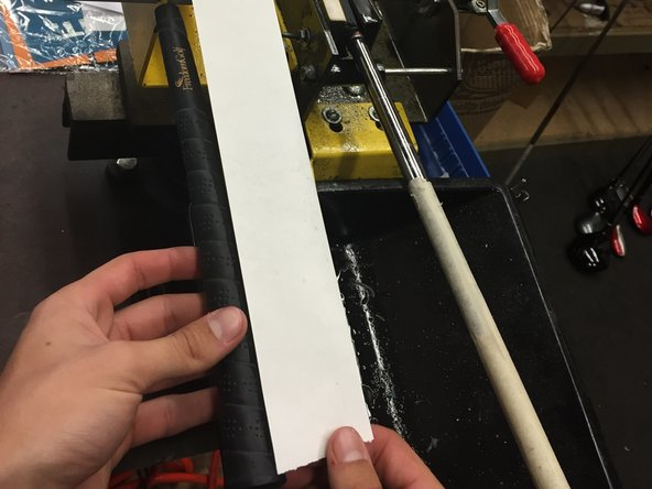 Measure the amount of double-sided tape necessary to cover the area of your grip.