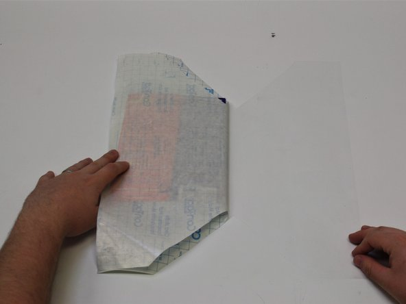 Image 2/3: Fold the edge of the laminate film onto the table to prevent sliding and bubbles.