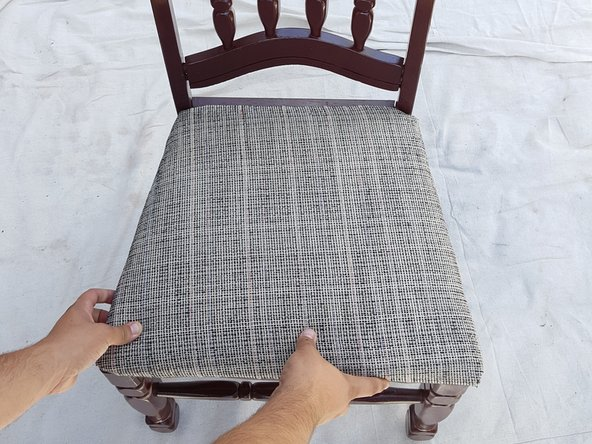 Grab your newly covered cushion and place it on the seat of the chair frame.