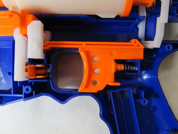 Image 2/3: Remove the spring from the rear of the trigger.