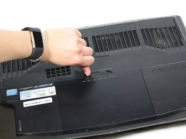 Flip the laptop over and slide the battery release latch to the right.