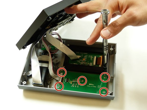 Remove the five 7mm PH #1 screws from the back of the keypad, by rotating the screw driver counter clockwise, removing the screw from the housing completely.