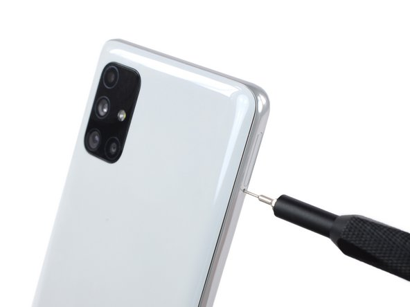 Insert a SIM eject tool into the small hole on the SIM card tray on the left edge of the phone.