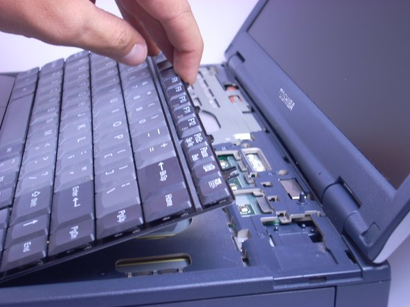 Image 1/1: The keyboard is still connected to the laptop by a ribbon. Place the keyboard gently on top of the trackpad, keys side down.