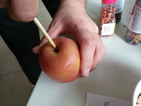 Insert the stick into the apple near the stem.