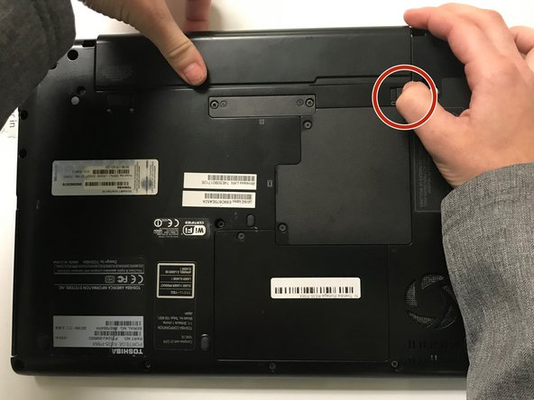 Hold the unlock clip while pulling the battery away from the laptop.