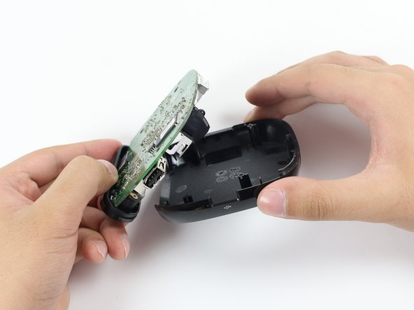 Use your fingers to carefully lift the motherboard from the top half of the device.