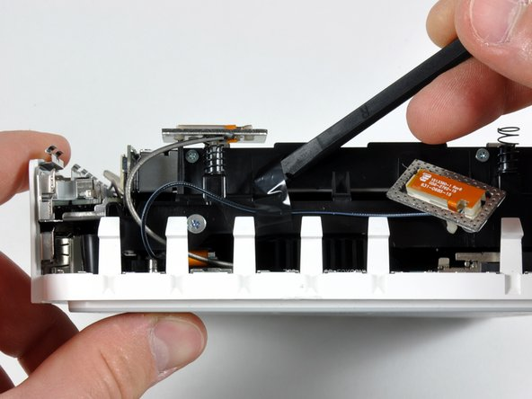 Use a spudger to peel back the black tape and release the antenna cable.