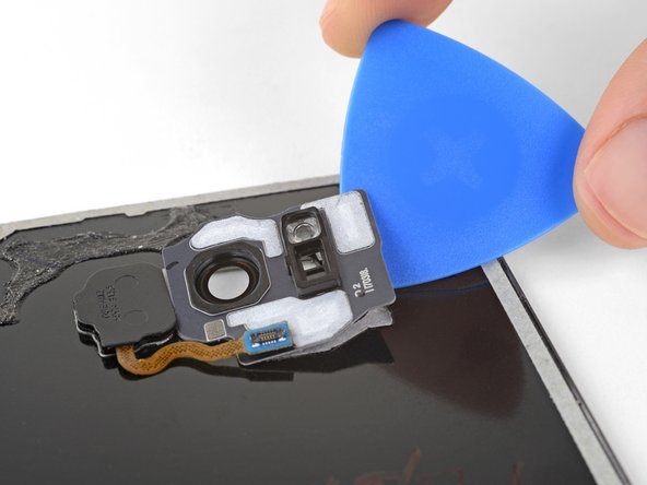 Use an opening pick to pry the camera bezel away from the rear glass.