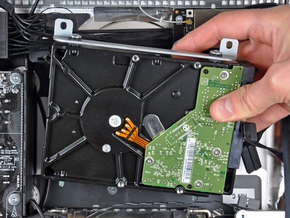 Image 2/2: Lift the hard drive off its two lower positioning pins and remove it from the outer case.