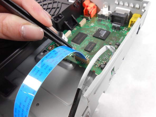 Using the plastic tweezers, carefully remove the ribbon cable from the motherboard.