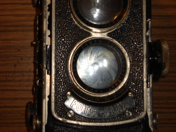 Image 1/3: Set the distance wheel to infinity. The front plate comes off easily by loosening the four screws (two above the lenses, two below the badge). Newer versions may need to have removed their focus lever first.