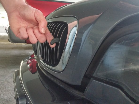 Walk around to the front of the car and pull upward on the latch protruding from the grill.