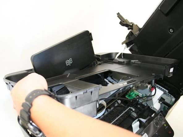 Remove the scanner unit with the plastic cover by lifting it up from the bottom portion of the printer.