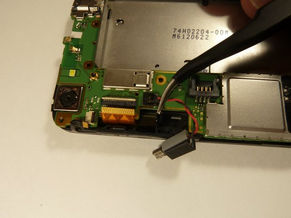 Using the tweezers, pull up on the connecting wires detaching the vibrator from the motherboard.