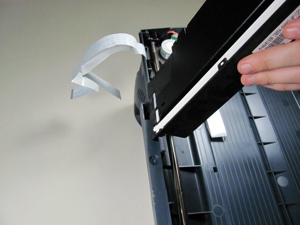 Image 2/2: Remove the scanner head from the scanner by gently rotating and then lifting.