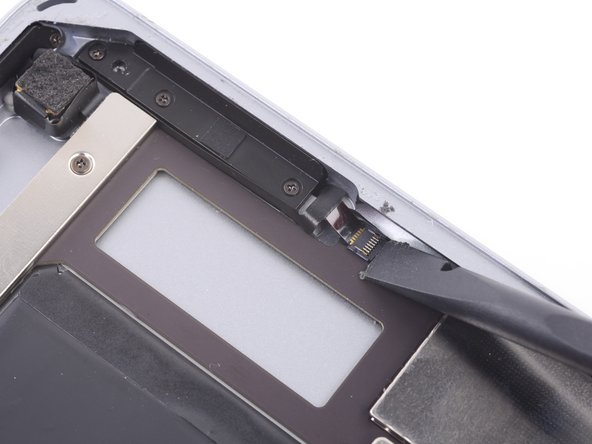 Use the flat end of a spudger to flip up the retaining flap on the case buttons' ZIF connector on the logic board.