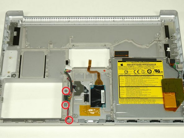 Image 1/1: Remove a third Phillips screw near the front of the computer that pins down a ground loop.