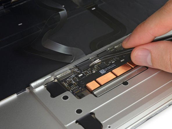 Use tweezers to peel back the tape covering the trackpad cable ZIF connector.