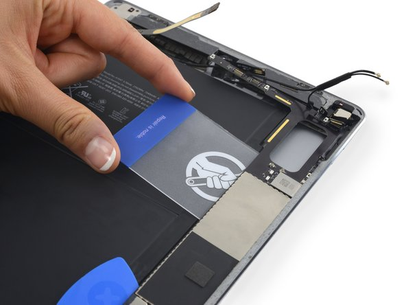 Image 2/3: Slide the card down the length of the logic board to release the adhesive.