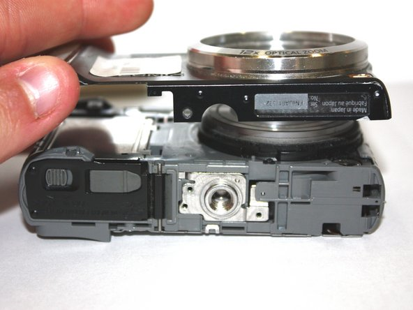 Carefully separate the front of the camera from the main body