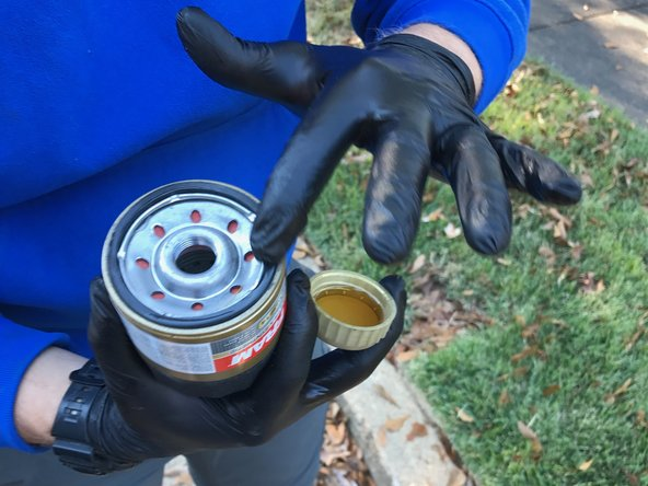 Image 2/3: Use your wetted finger to spread a thin layer of oil onto the gasket of the new oil filter.