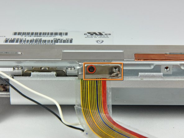 Remove the small Phillips screw from behind the display data cable.