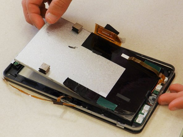 Use a plastic opening tool to wedge underneath the digitizer and pry up, lifting the digitizer out of the frame.