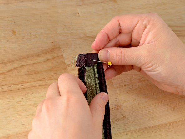Fold the top of the webbing down over the sewn zipper tape.