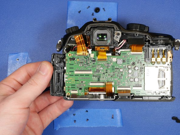 The PCB should now be relatively lose inside the camera.