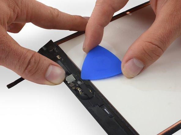 ケーブルとデジタイザの間に開口ピックを挿入して、ホームボタンリボンケーブルを固定しているテープの最後の部分をはがします。