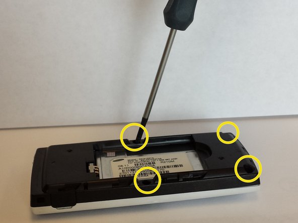 """After removing the battery, unscrew the 4 3/16"""" screws on the black plastic cover with the Phillips #00 Screwdriver."""