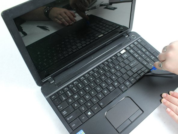 Use the plastic opening tool to remove the keyboard from the laptop.